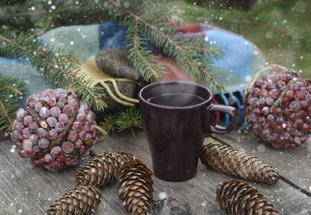 Ð¡up of hot tea on a rustic wooden table. Still life of cones, twine, patskthread, fir branches. Preparing for Christmas.  Effect Drawn Snow