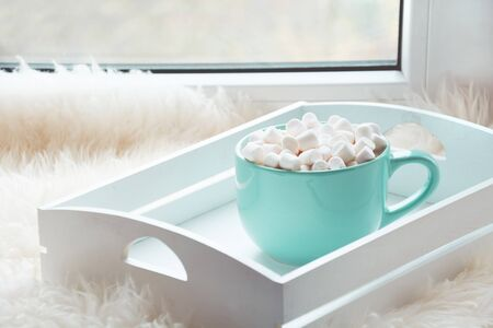 Blue cup of hot chocolate with marshmallow on windowsill with furskin for relax. Holiday concept. Home style. Stock Photo