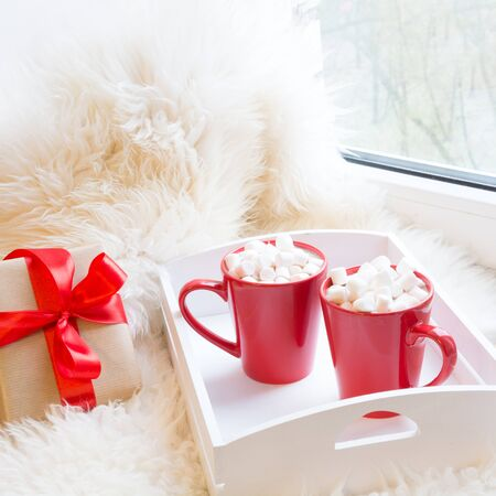 Two red cup of hot chocolate with marshmallow on white windowsill with furskin for rest. Holiday. Christmas time. Stock Photo