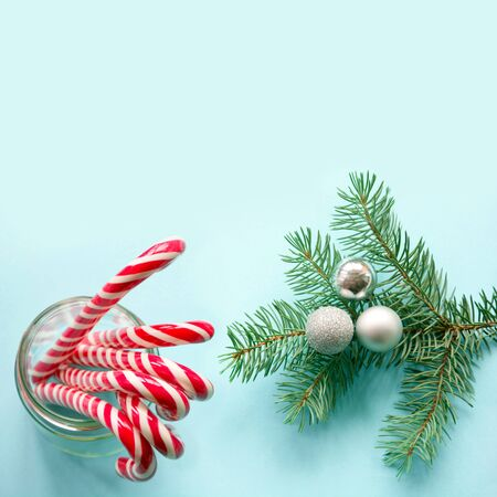 Christmas decoration with candy canes in glass with evergreen tree on blue background. Christmas background. Stok Fotoğraf