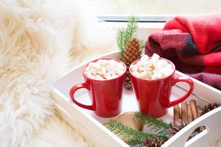Red cup of hot chocolate with marshmallow on windowsill. Weekend concept. Home style. Christmas morning. Stock Photo
