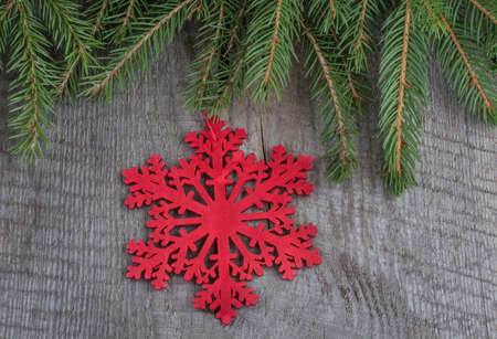 Red christmas snowflakes on wooden background with fir branches. Stock Photo