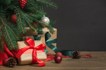 Christmas holiday background. Gifts with a red ribbon, Santas hat and decor under a Christmas tree on a wooden board. Close up. Copy space on chalkboard.