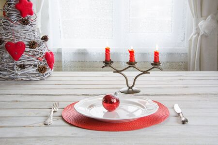 Christmas place setting with white dishware, cutlery, silverware and red decorations on white wooden board in ligth interior near the window. Christmas candlestick with red candles as decor.