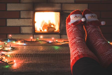 Voeten in wollen rode sokken bij de openhaard. Vrouw ontspant bij warm vuur en opwarmt haar voeten in kerstsokken. Close-up op de voeten. Tafelblad voor weergave van uw kerstproduct. Kerstvakantie.