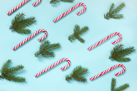 Christmas candy cane lied evenly in row on blue background. Flat lay and top view. Pattern. Stock Photo