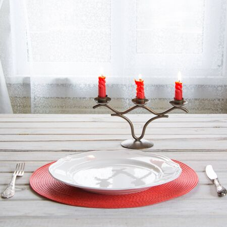 Christmas place setting with white dishware, cutlery, silverware and red decorations on white wooden board in ligth interior near the window. Candlestick with red candles as decor.
