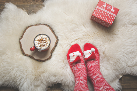 Woman in warm christmas knitted socks wants to drink coffee and open a gift. Mug with coffee and gift on white sheep skin rug. Winter weekend concept, top view. View from above.