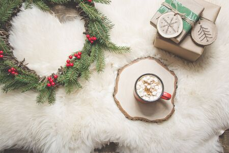 Christmas holiday card. Cup of coffee, wreath, handmade gifts. Rest at home. Top view. Copy space. Matte image
