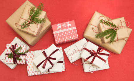 Christmas gifts wrapped in ornament paper and decorative red rope ribbon on red surface. Creative hobby, top view. Prepare to Xmas.