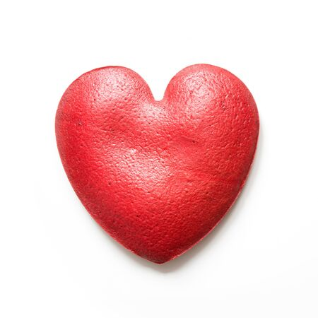 A cake of red velvet in the shape of a heart. View from above.