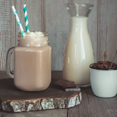 Chocolate coffee milkshake with whipped cream served in glass mason jar on gray wooden background. Summer sweet drink. Square image. Stock fotó