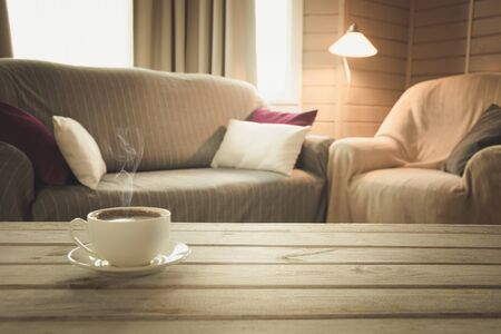 Hot coffee on tabletop in modern living room in rustic style with chair, soft divan. Blurred abstract background for design.