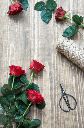 Red roses bouquet on a wooden table. View from above. Rustic style. Top view.