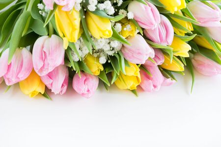 Beautiful bouquet of pink and yellow tulip on white. Close up. Top view. Copy space. Stock Photo