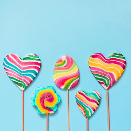 Set of five rainbow colorful lollipops isolated on blue background. Stock Photo