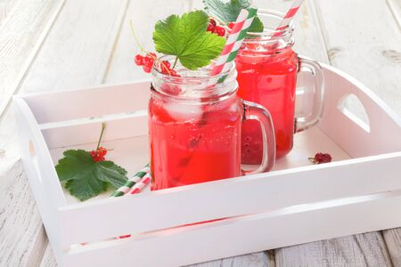 Summer homemade red currant lemonade in a mason jar with decor of berry in tray on ligth wooden table. Close up.