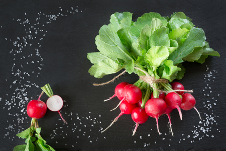Bunch of fresh radish on black dish. Top view. Copy space. Close up.