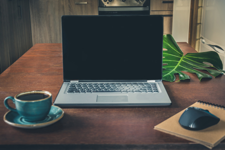 Workplace with open laptop with copy space, cup of coffee on wooden desk for remote work in rustic or colonial style. Copy space.