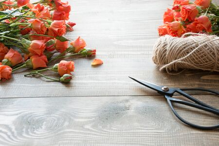 Working table florista.Preparation a bouquet of orange shrub roses. Close up. Stock Photo