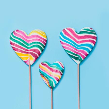 Three lollipops rainbow candy as heart on blue. Stock Photo