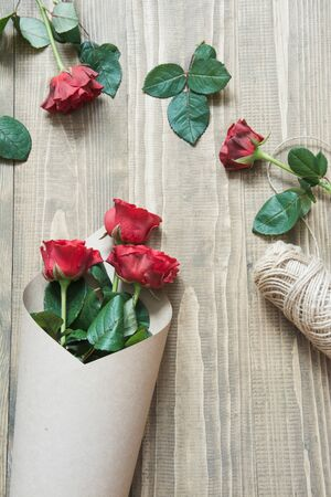 Wrapping a red roses bouquet on a wooden table. View from above. Rustic style. Top view.