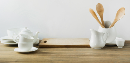White kitchen utensils, dishware and other different white stuff for serving on white wooden board. Copy space.
