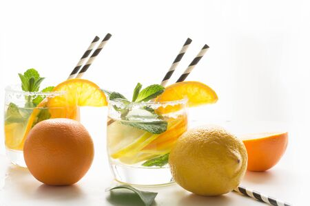 Summer detox lemonade. Water with lemon,orange, ice and mint in glassful on white. Close up.