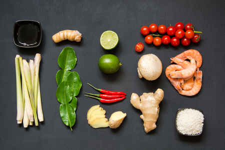 Ingredients for popular Thai soup Tom-yum kung. Lime, galangal, red chili, cherry tomato, lemongrass and kaffir lime leaf on black board . Flat lay. View from above.