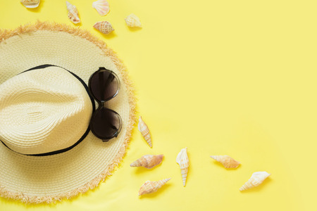 Straw beach fomans hat and black sun glasses with seashells on yellow background. Top view. Flat lay.