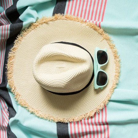 787a7ca5 Straw beach sun-hat and sun glasses on pastel pink and mint pareo. Female