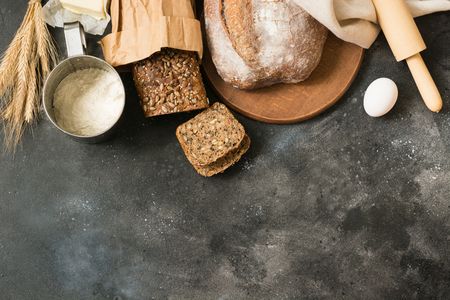 Various homemade rye bread and wheat on black stone table. Space for text. Top view.