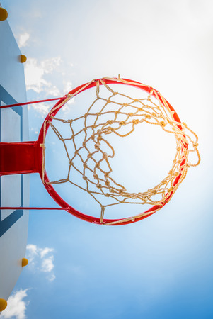 Basketball hoop with blue cloudy sky. Outdoor.