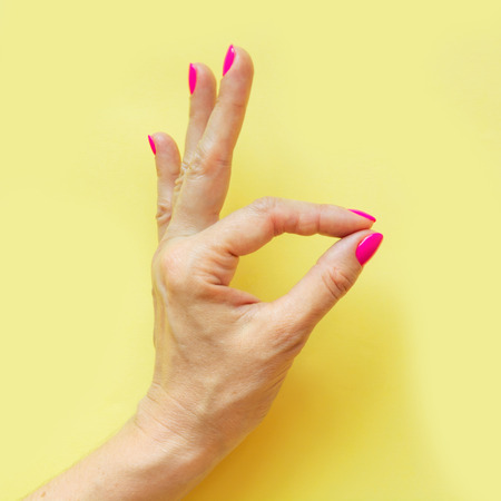 Female hand with pink nail on yellow. Concept. Trendy style. Spetial handbreadth - Ok. Concept.