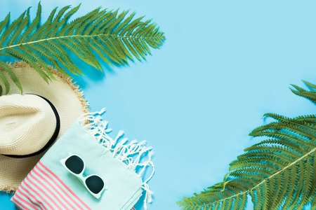 Tropacal vacation. Straw beach sunhat, sun glasses, beach towel, leaf of fern on blue background. Top view with copy space. Summer.