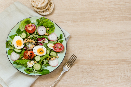 Healthy vegan lunch plate. Fresh salad with vegetables and eggs for proper nutrition. Summer food. Top view, copy space.