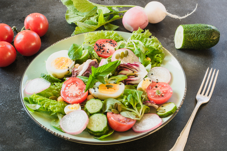 Healthy salad with vegetables and eggs on black table. Close up, copy space. Balanced diet for weight loss.