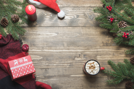 Christmas composition of wreath, cup of coffee on wooden board. Top view. Copy space.