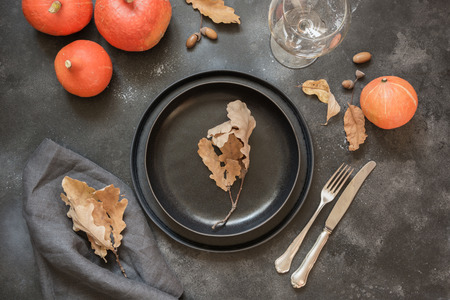 Thanksgiving Day or Halloween place setting with pumpkin on black table. Top view. Archivio Fotografico