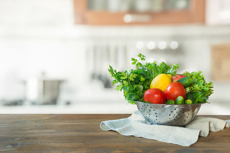 Modern kitchen with fresh vegetables on wooden tabletop, space for you and display products.