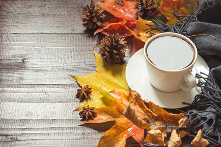 Autumn still life with cup of coffee,cone, cinnamon, warm scarf on wooden board. Copy space. Top view.