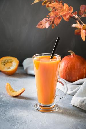 Fresh pumpkin spice smoothie or juice on dark. Autumn, fall or winter hot drink. Cozy healthy beverage.