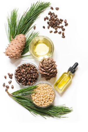 Cedar oil, branches and cedar cone on white background. Copy space. Beauty and healthy concept. 免版税图像