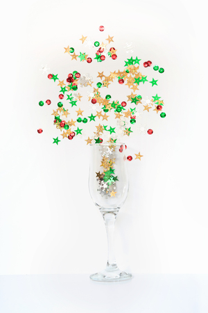 Colorful confetti in shape of stars poured out glasses of champagne on white. Top view. Christmas party. Magic night.