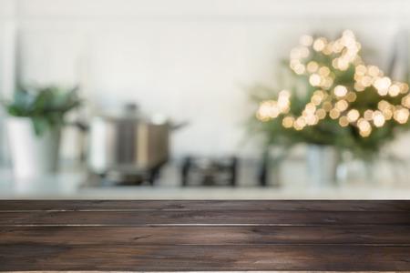 Leeg houten tafelblad voor weergaveproducten en wazige keuken met kerstboom als achtergrond.