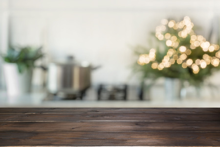 Empty wooden tabletop for display products and blurred kitchen with Christmas tree as background. Standard-Bild