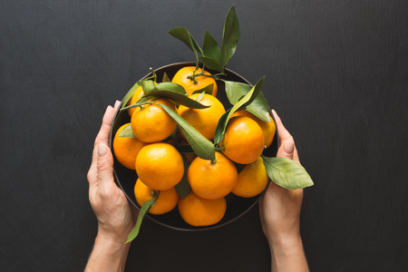 Fresh mandarins with leaves in female hand on black. Healthy eating concept. Copy space. Top view.