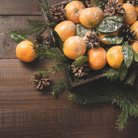 Fresh mandarins with leaves on wooden board. Christmas composition with copy space. Top view.