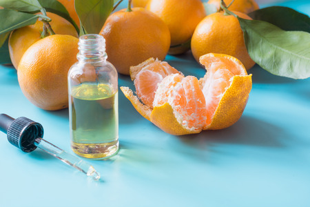 Essential oil of orange mandarin in glass bottle over pastel blue background. Spa and wellness concept.