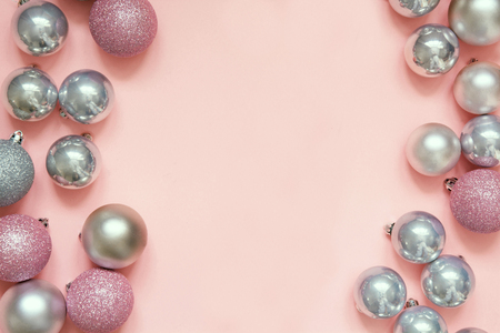 Christmas pink and silver baubles as frame on pastel pink background. Top view with space for text.